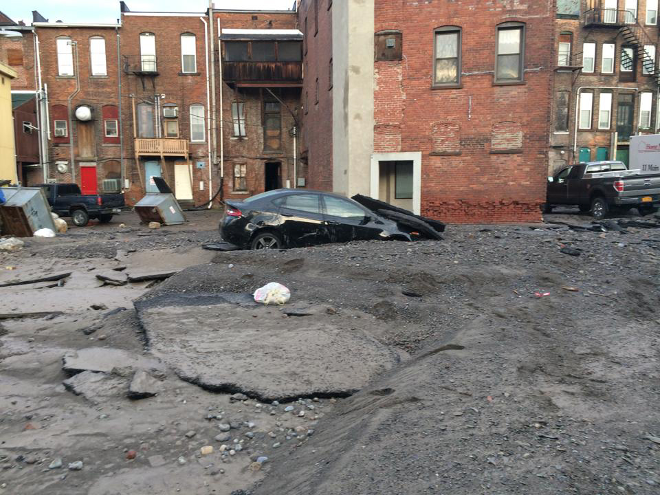 Car in the Pavement behind the Owl's Nest on Basin St. Photo via Jeff Gifford